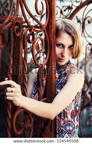 portrait of a girl near the old gate - stock photo
