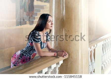 portrait of a girl on a balcony with columns - stock photo