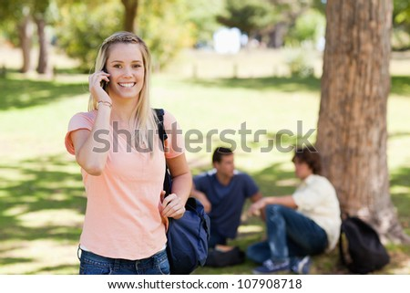 Portrait of a girl on the phone in a park with friends in background