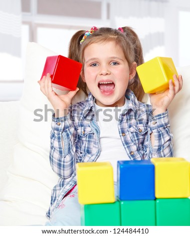 portrait of a girl playing with blocks, sitting on the couch at home - stock photo