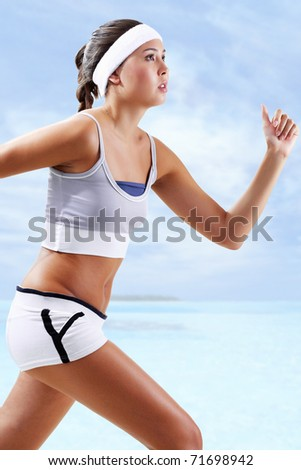 Portrait of a girl running against blue background