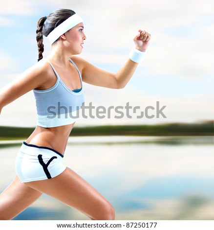 Portrait of a girl running by the lake in summer - stock photo