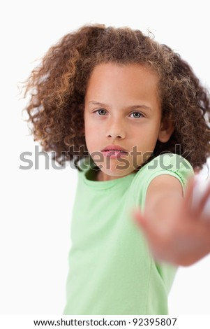 Portrait of a girl saying stop with her hand against white background - stock photo