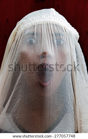 portrait of a girl screaming behind the veil - stock photo