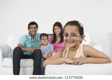 Portrait of a girl smiling with her family in the background