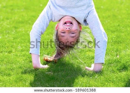 Portrait of a girl standing upside down playing on green grass outdoors in spring park - stock photo