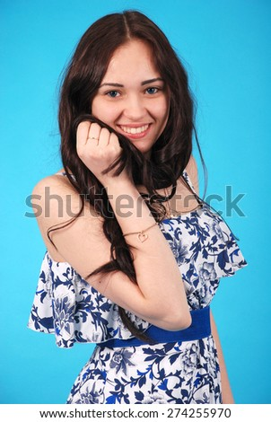 Portrait of a girl-teenager on blue studio background - stock photo