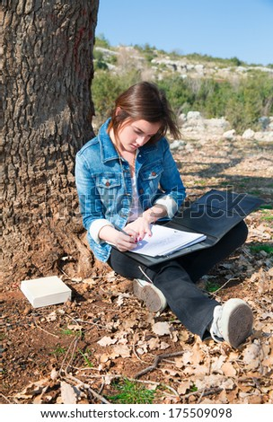 Portrait of a girl teenager reading book and writing