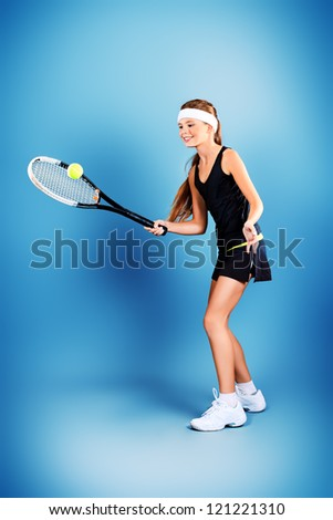 Portrait of a girl tennis player holding tennis racket and tennis ball. Studio shot.