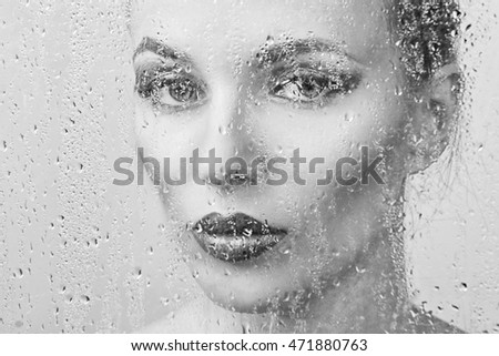 Portrait of a girl through wet glass with drops of water