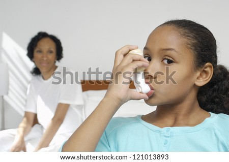 Portrait of a girl using asthma inhaler with mother in background