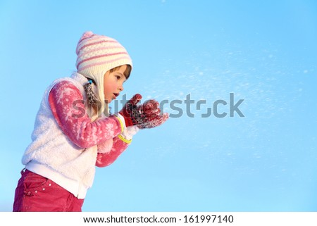 portrait of a girl walking around outdoors in the winter, blowing on snow - stock photo