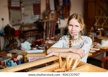Portrait of a girl weaver in the workshop, standing at the loom