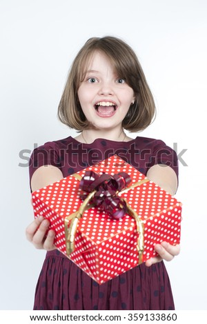 Portrait of a girl who holds a gift to the viewer. Studio photography on a light gray background. Age of child 10 years. - stock photo
