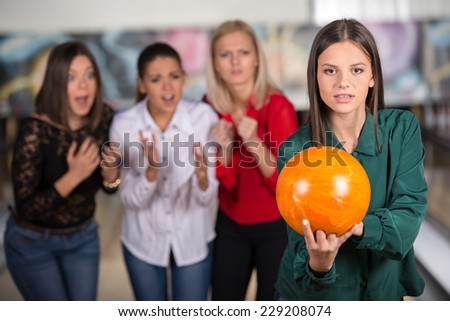 Portrait of a girl who is getting ready to throw the ball against the background of her friend.