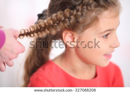 Portrait of a girl whose long braided pigtail, close-up