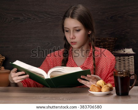 Portrait of a girl with a big book. She reads with interest. In the circle the table with a drink, sweets for tea. The girl is young, beautiful, with long braids