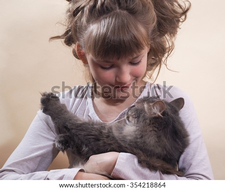 Portrait of a girl with a cat. Young, beautiful girl hugging cat. Cat likes to caress the cat likes to lie in the hands of man. Cat gray, fluffy.  The girl has a beautiful face and hair