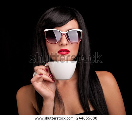 Portrait of a girl with a cup on a black background. - stock photo