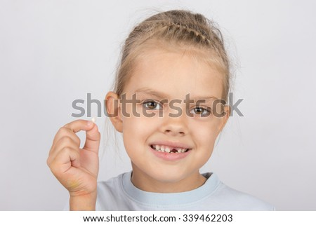 Portrait of a girl with a fallen tooth in his hand