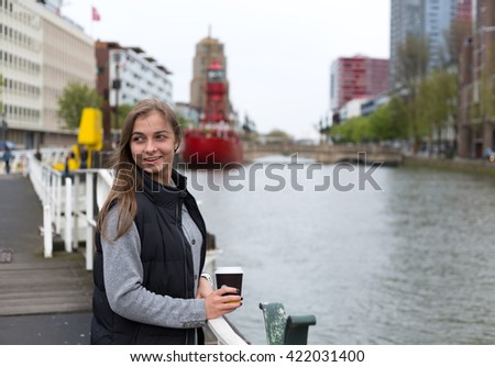 Portrait of a girl with a glass of coffee on a bridge in Rotterdam. - stock photo