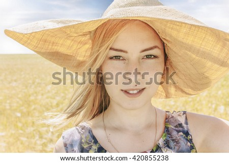 portrait of a girl with a hat in summer field. attractive blond woman in flower dress and wide-brimmed hat. close up. looking at the camera - stock photo