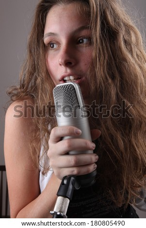 portrait of a girl with a microphone in the studio