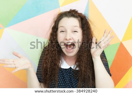 portrait of a girl with an emotion of admiration and wonder on a colored background