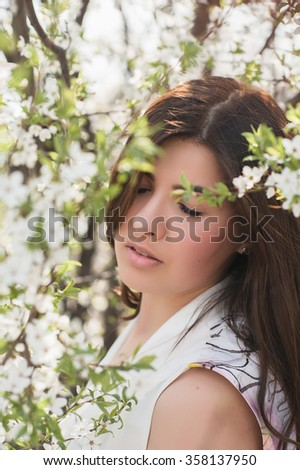 Portrait of a girl with beautiful hair in the lush spring garden, beauty, makeup, hair, - stock photo