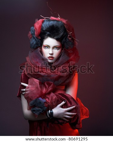 Portrait of  a girl with creative make-up and in red shawl - stock photo