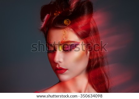 portrait of a girl with creative make-up. The girl in the red dress. Red lipstick and feathers in her hair.