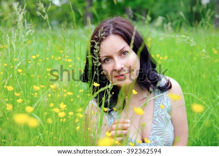 Portrait of a girl with flowers. Girl outdoors in a field of flowers. Flower meadow. Country landscape.. - stock photo