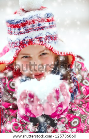 portrait of a girl with hat and scarf outdoor in snow - stock photo