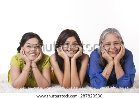 Portrait of a girl with her mother and grandmother lying on carpet over white background - stock photo