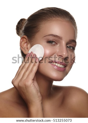 Portrait of a girl with pure and healthy glowing skin without makeup, who is doing daily cleansing procedures using a cotton pad after shower, wellness and spa, white isolated background