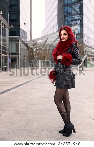 portrait of a girl with red hair, leather jacket, skirt and cuffs and collar of red feathers in a urban scene