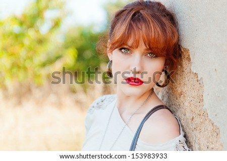 portrait of a girl with red hair, red lips and green eyes against the wall in the background green trees, look at the camera, horizontal frame