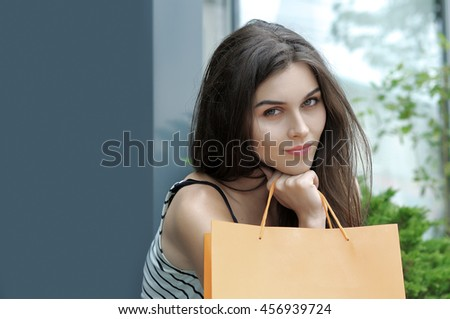Portrait of a girl with shopping bags. She is wearing a striped shirt and enjoying life - stock photo