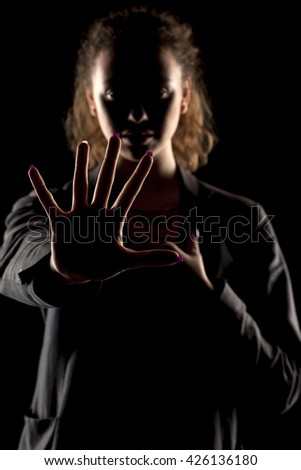 portrait of a girl with the face in a shadow showing stop hand