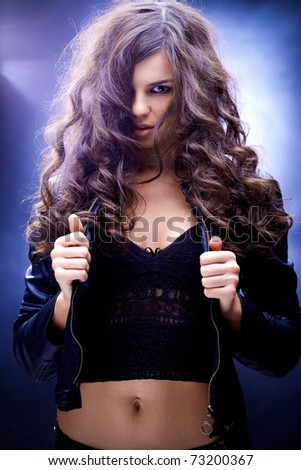 Portrait of a girl with wavy hair against blue background