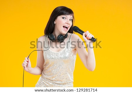 Portrait of a glamorous caucasian girl holding mike and singing - stock photo