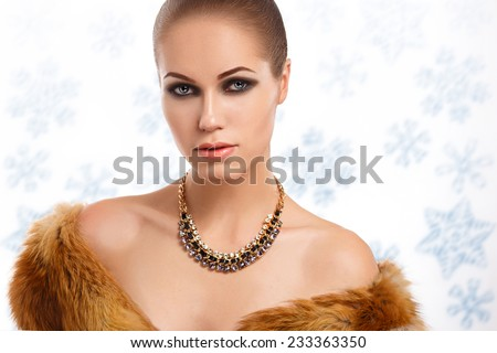 portrait of a glamorous girl in a fur coat on a background of snowflakes - stock photo