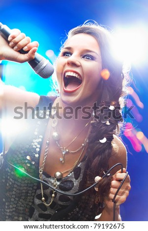 Portrait of a glamorous girl singing - stock photo