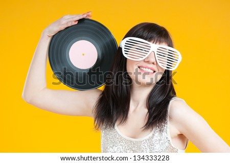 Portrait of a glamorous girl with a vinyl disc, yellow background - stock photo
