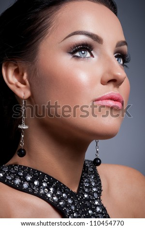 Portrait of a glamourous brunette girl with evening make up and long lashes - stock photo