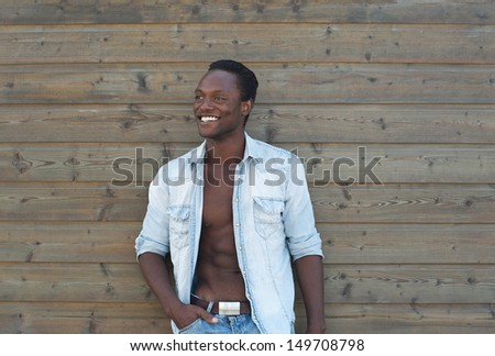 Portrait of a good looking black man smiling outdoors against wooden wall