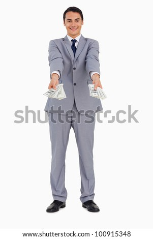 Portrait of a good-looking man giving a lot of dollars against white background