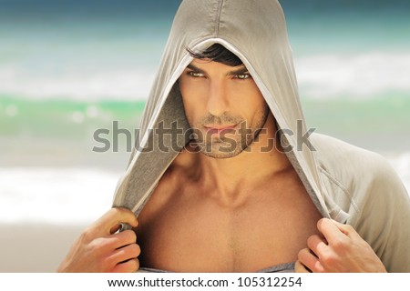 Portrait of a good looking man in athletic hood sportswear outdoors - stock photo