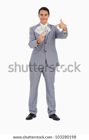 Portrait of a good-looking man showing a lot of dollars against white background - stock photo