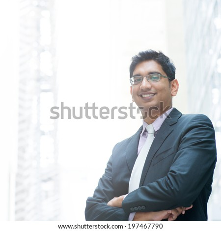 Portrait of a good looking smiling Indian businessman crossed arms standing at modern building, with natural light. - stock photo